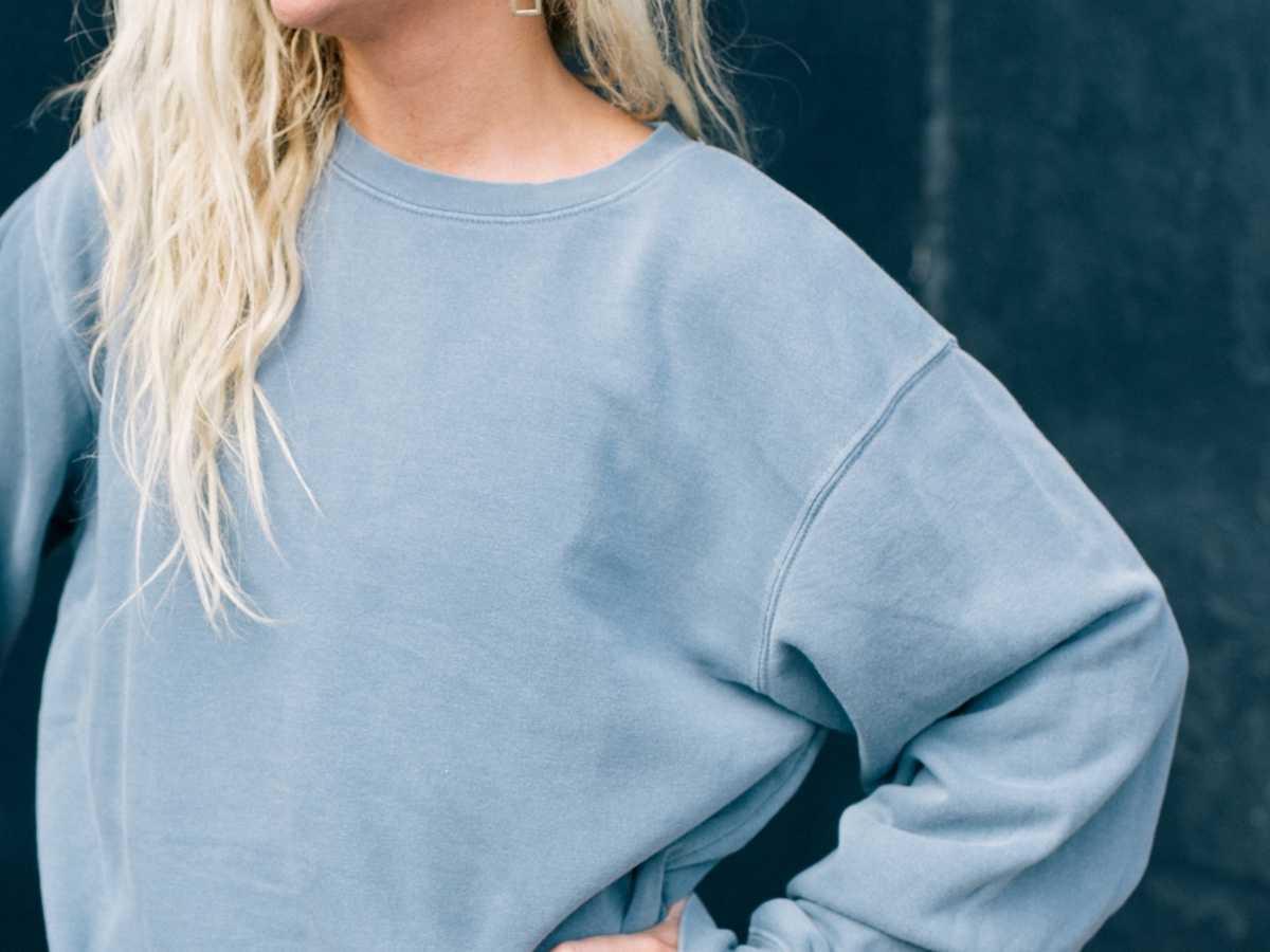 A blonde-haired girl wears a steel blue pullover sweatshirt.