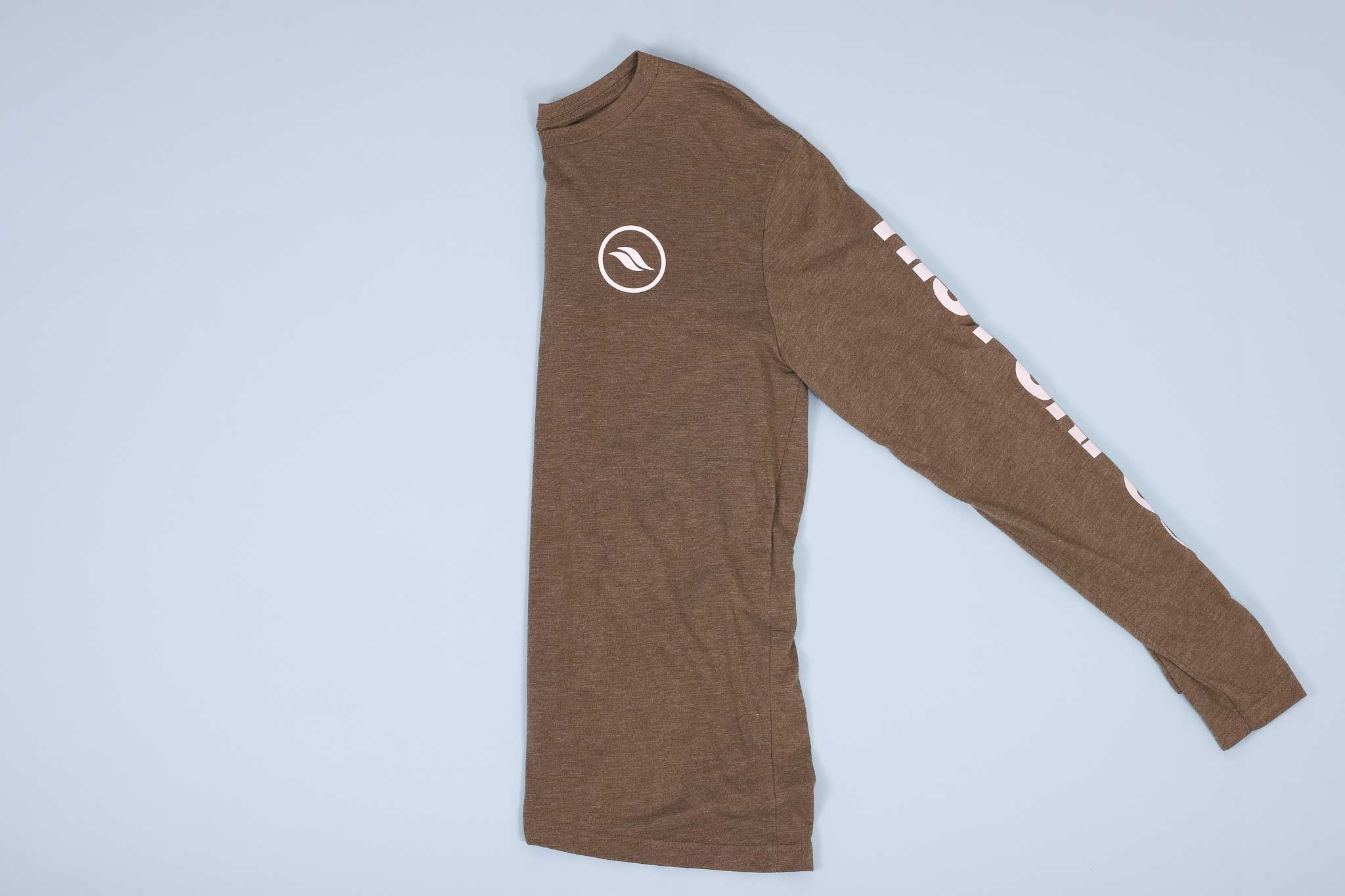 Olive long sleeve shirt with white text on the sleeves folded in half on a light blue background