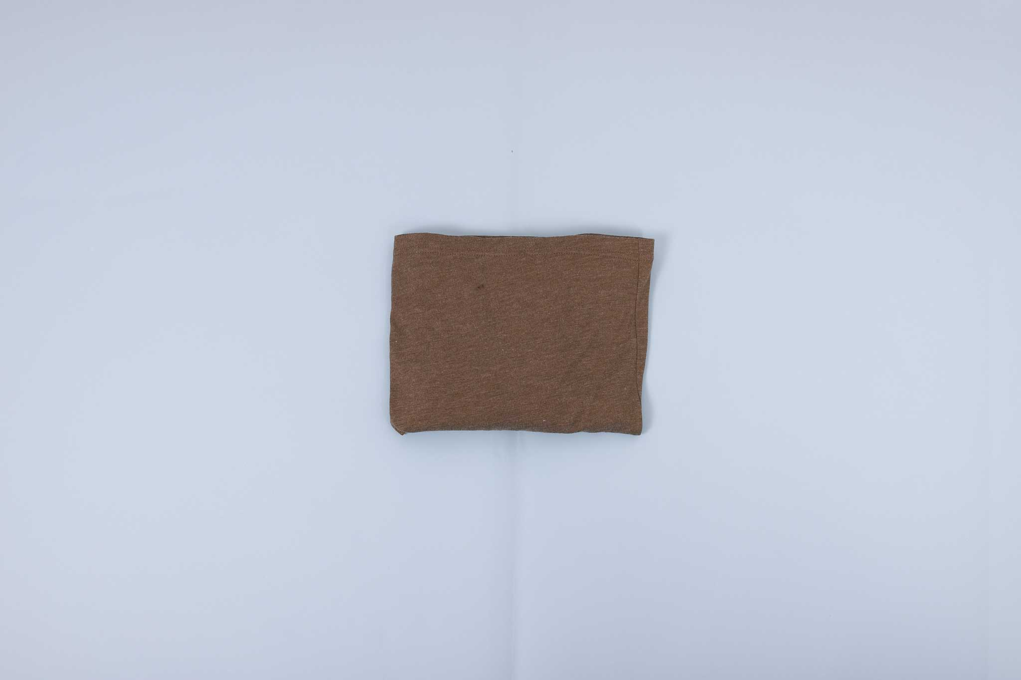 Olive long sleeve shirt folded into a rectangle on a light blue background