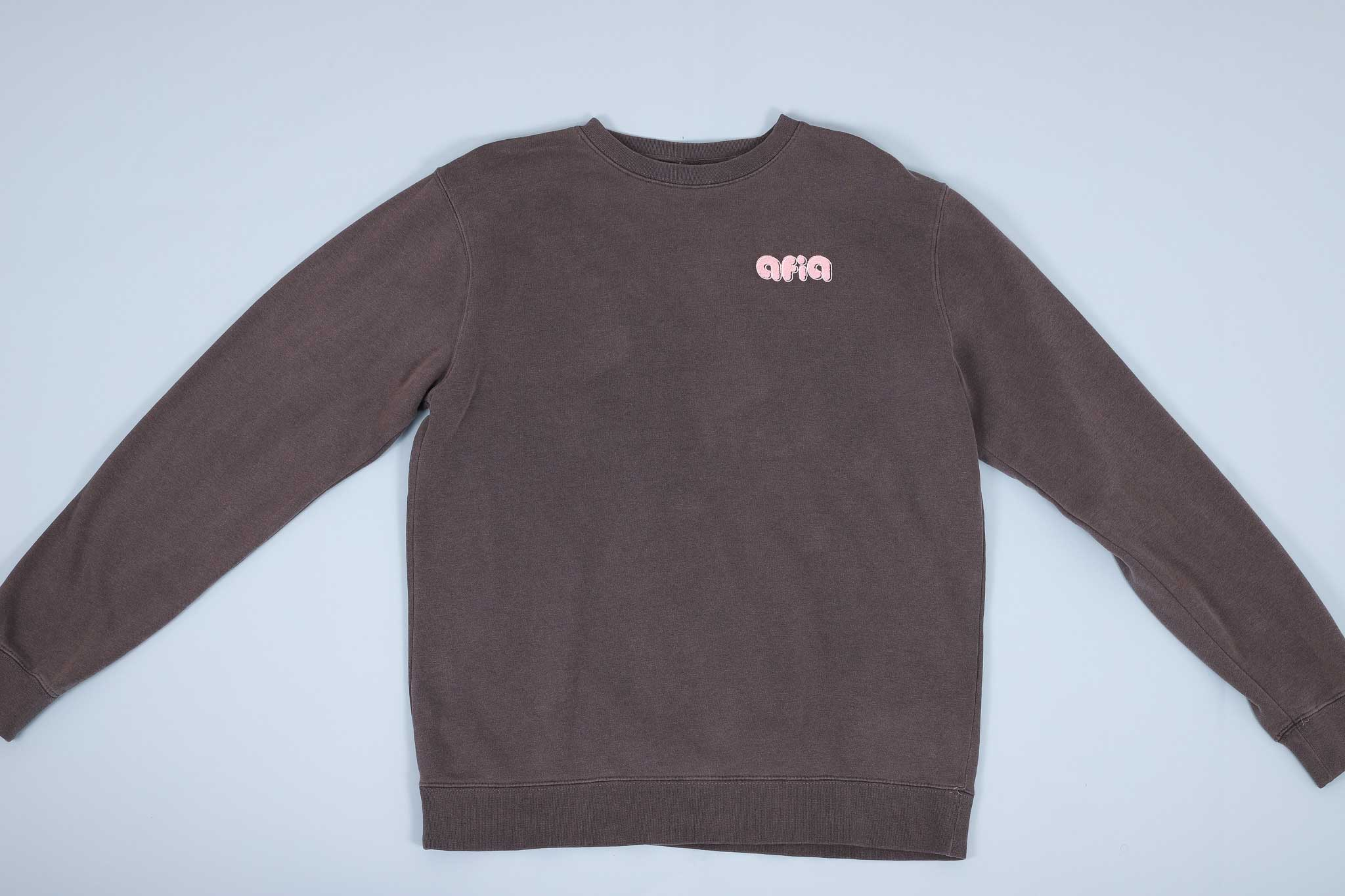 Grey sweater with pink text on the chest spread out on a light blue background