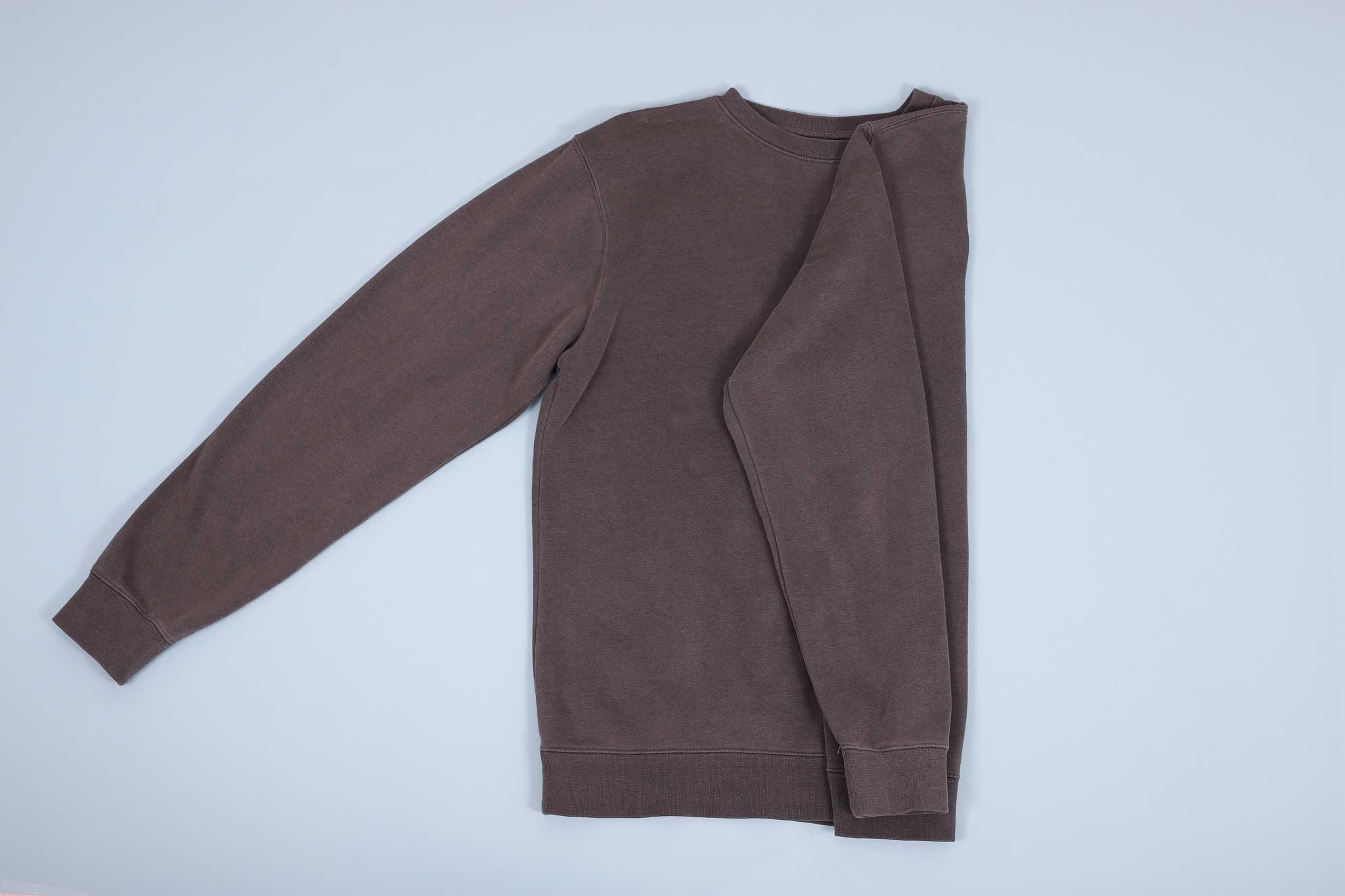 Grey sweater with sleeve folded in and then down towards the hem