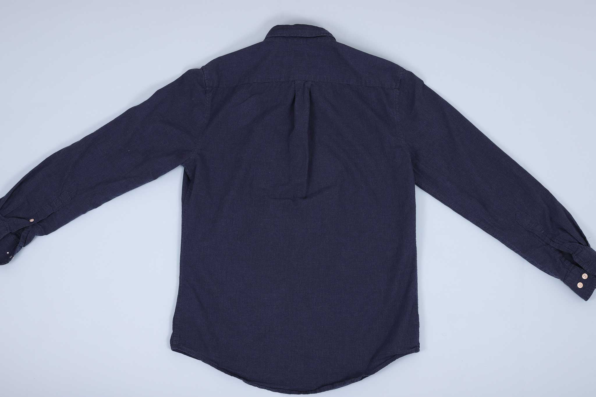 Navy buttoned up shirt spread out facing down against a light blue background