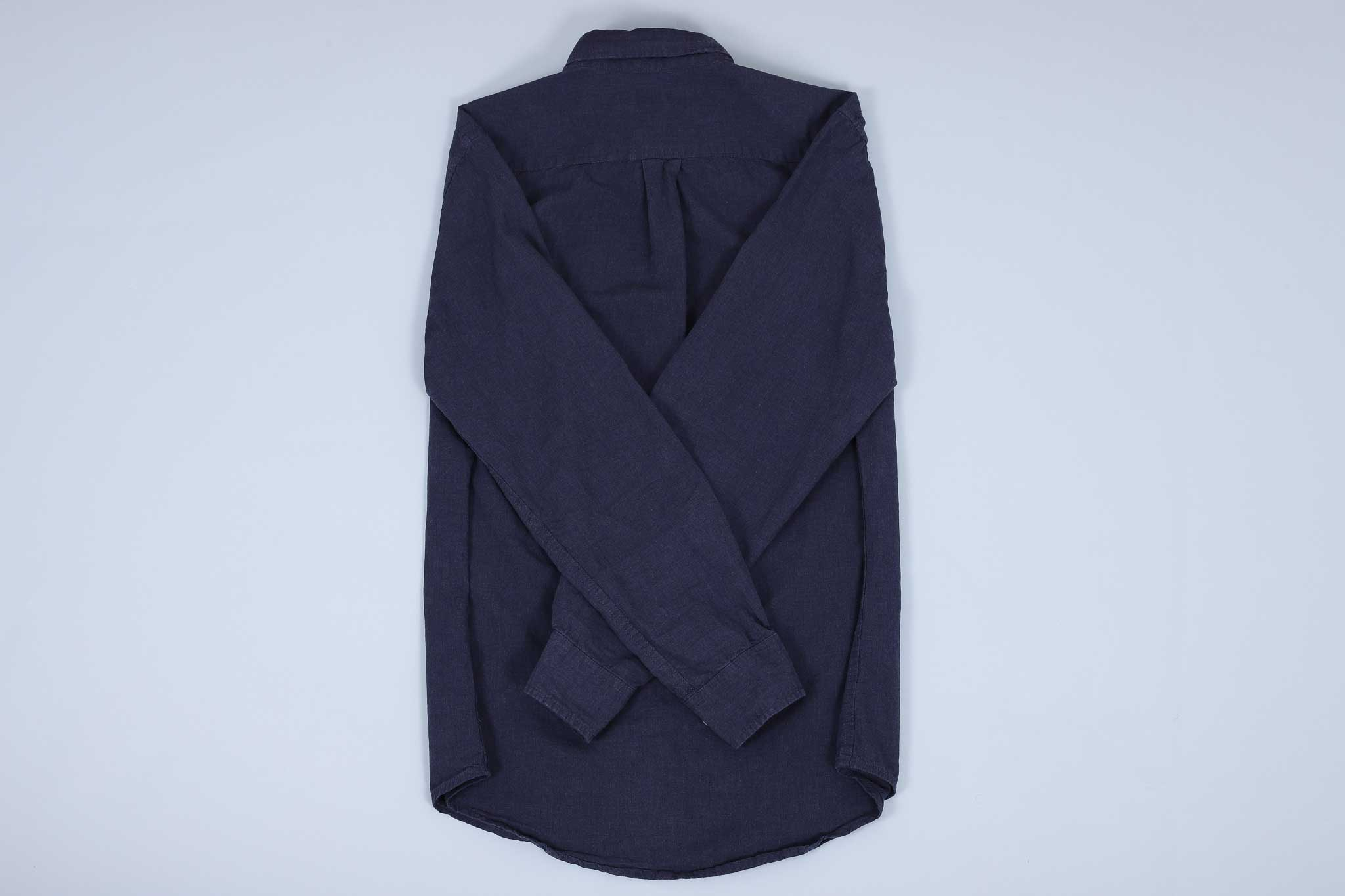 Navy buttoned up shirt with both sleeves crossed over each other on the back