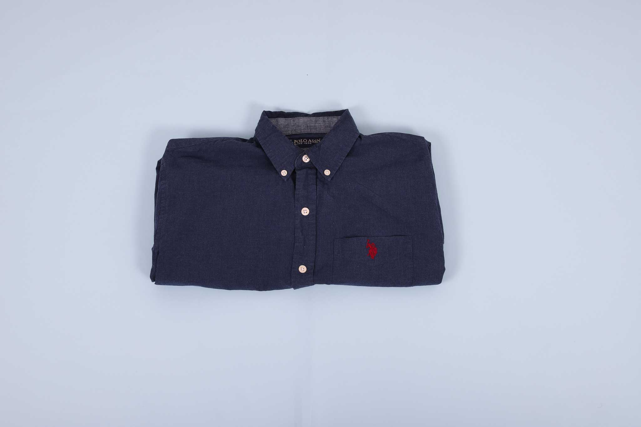Navy buttoned up shirt folded into thirds agains a light blue background