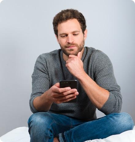 Mann sitzt auf einem Hocker und schaut auf sein Mobiltelefon.