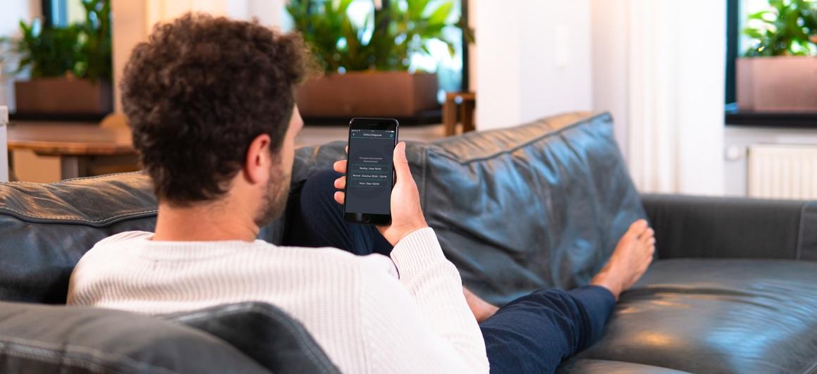 Mann sitzt auf dem Sofa und schaut auf sein Mobiltelefon