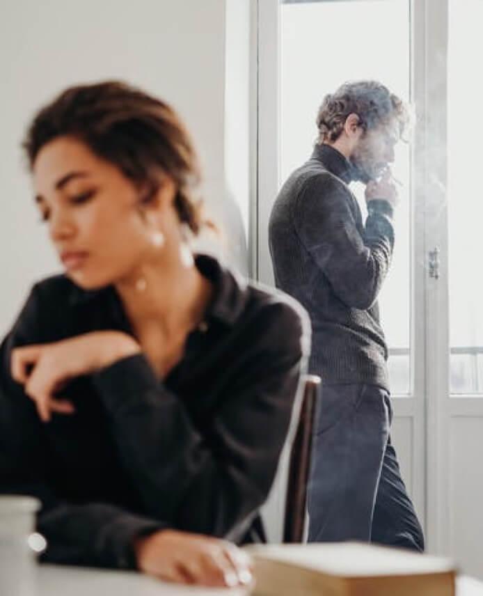 Mann raucht am Fenster