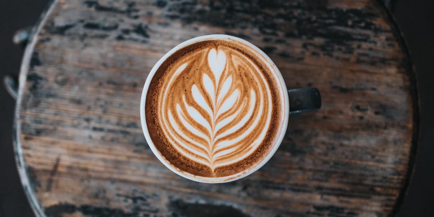 Lattekaffee auf einem Holzbrett | Nathan Dumlao - Unsplash