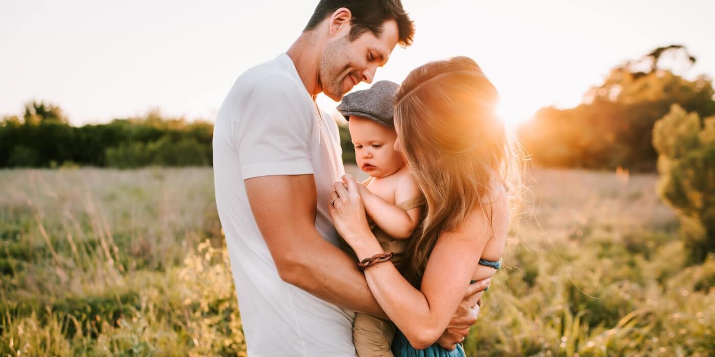 Glückliche Familie auf der Wiese bei Sonnenuntergang | Jessica Rockowitz - Unsplash