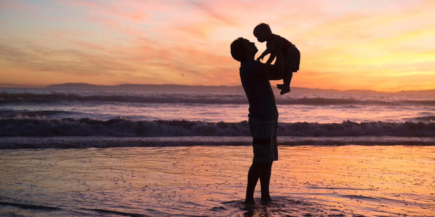 Vater hält sein Kind beim Sonenuntergang in die Luft |Jude Beck - Unsplash