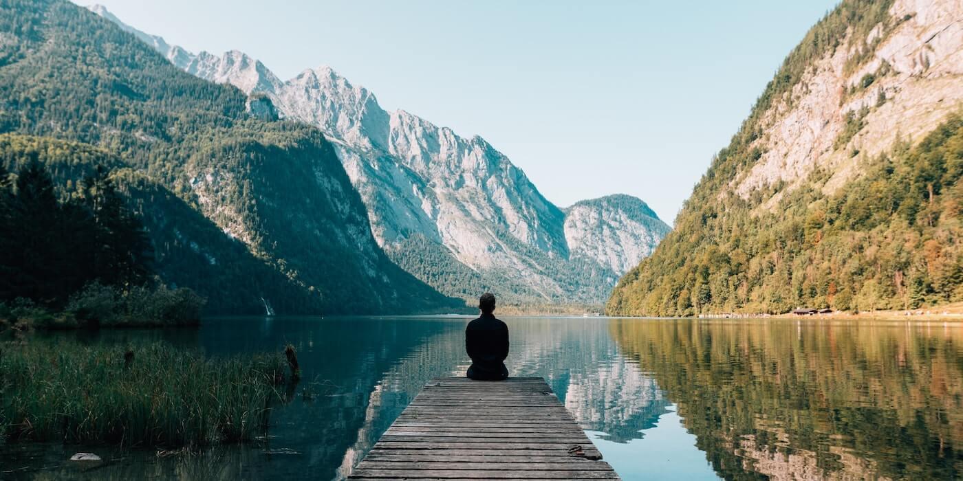 Mann sitzt auf dem Steg