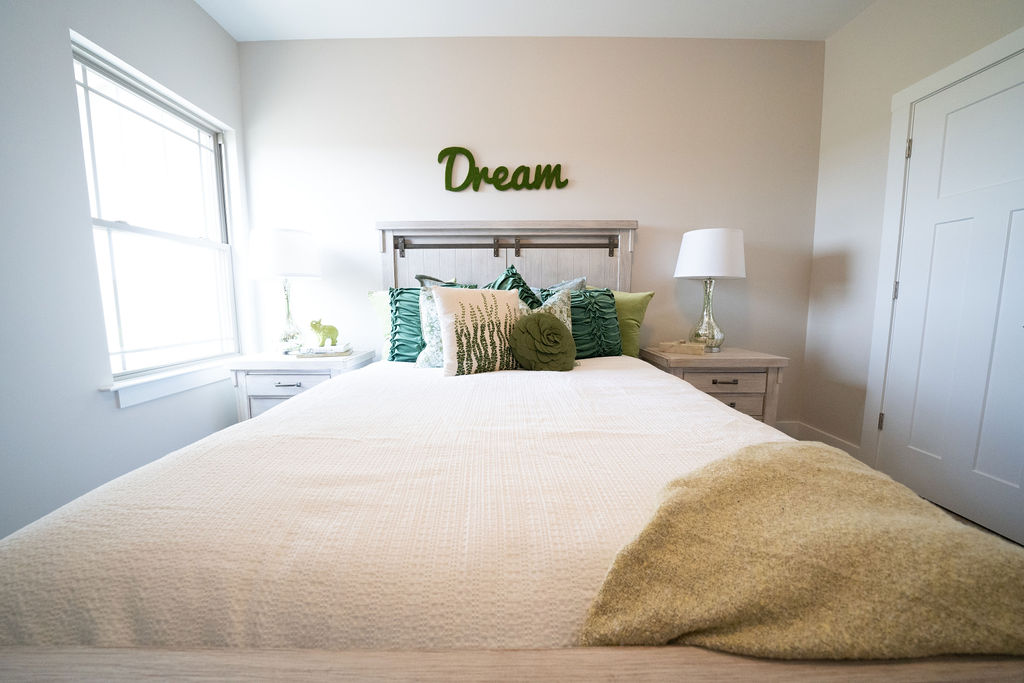 """Close-up of bed in master bedroom with overhead sign that says """"Dream"""""""