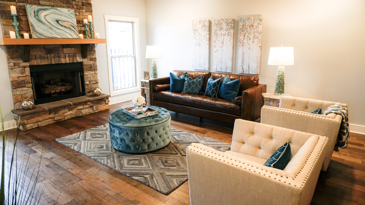 Living room with couch, two chairs, fireplace, and decorations
