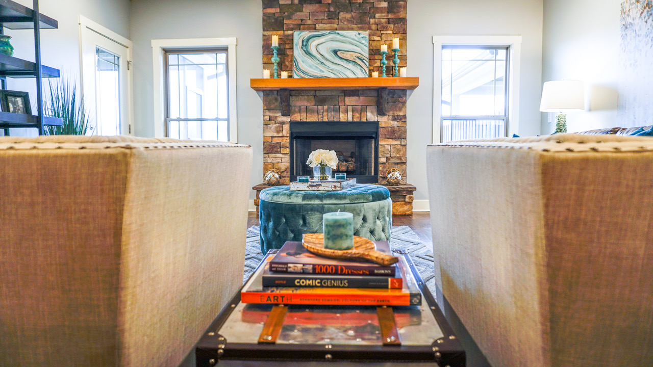 View of fireplace and books between two chairs