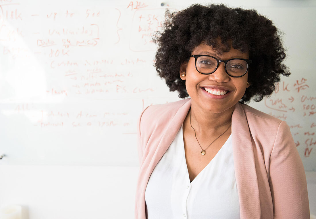 woman smiling in front of whiteboard