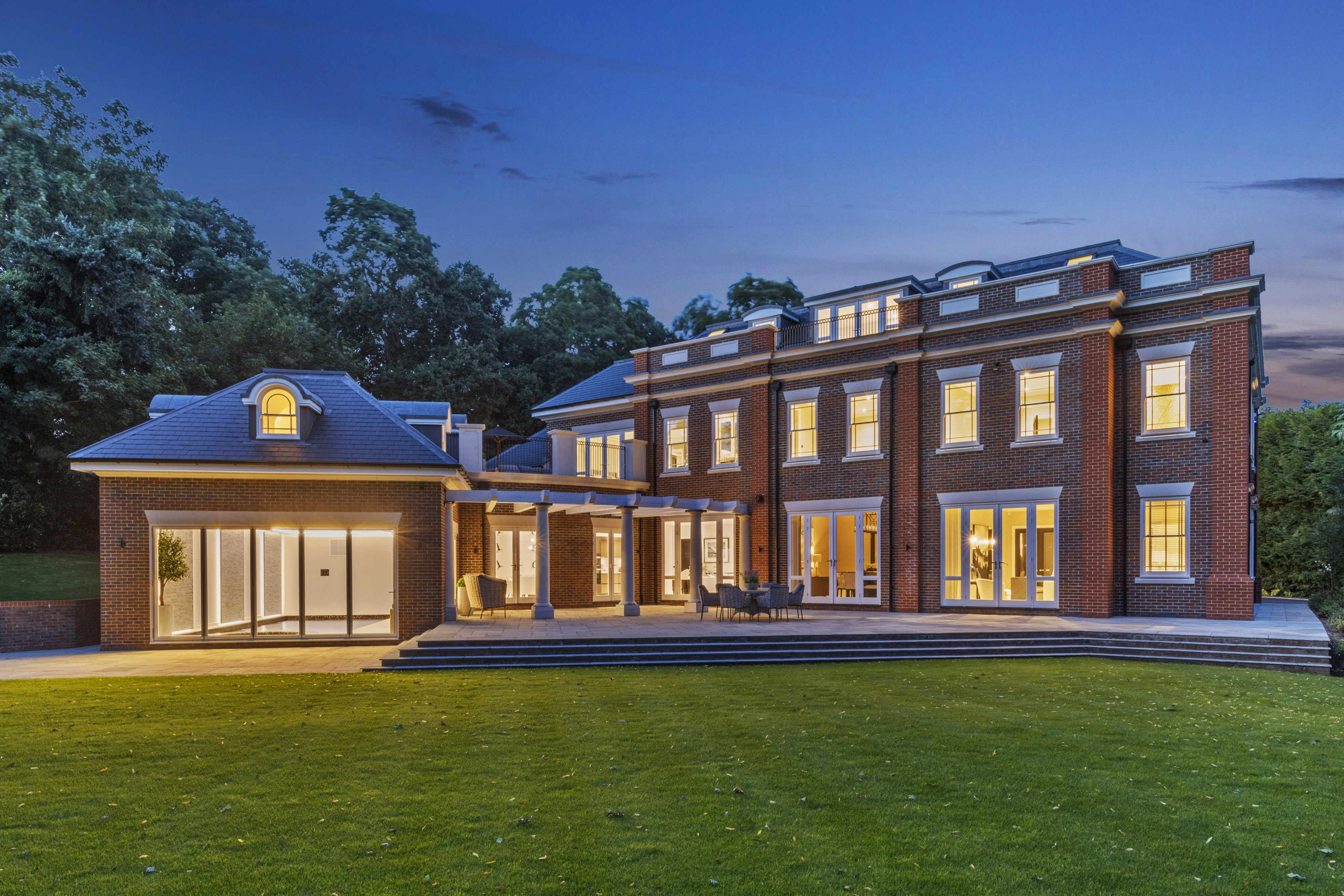 Rear elevation of red brick mansion at dusk