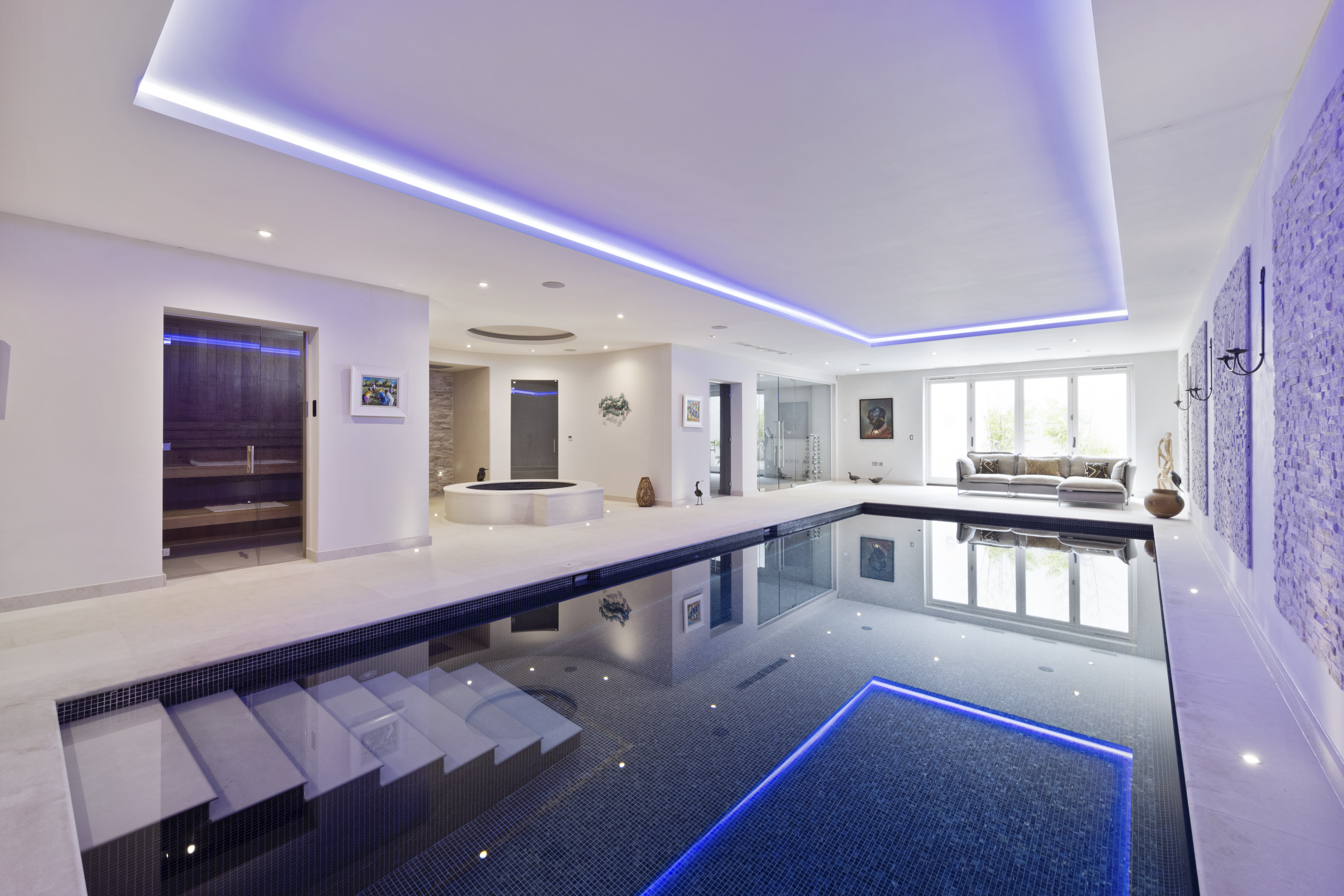 a luxurious indoor pool with blue mood lighting