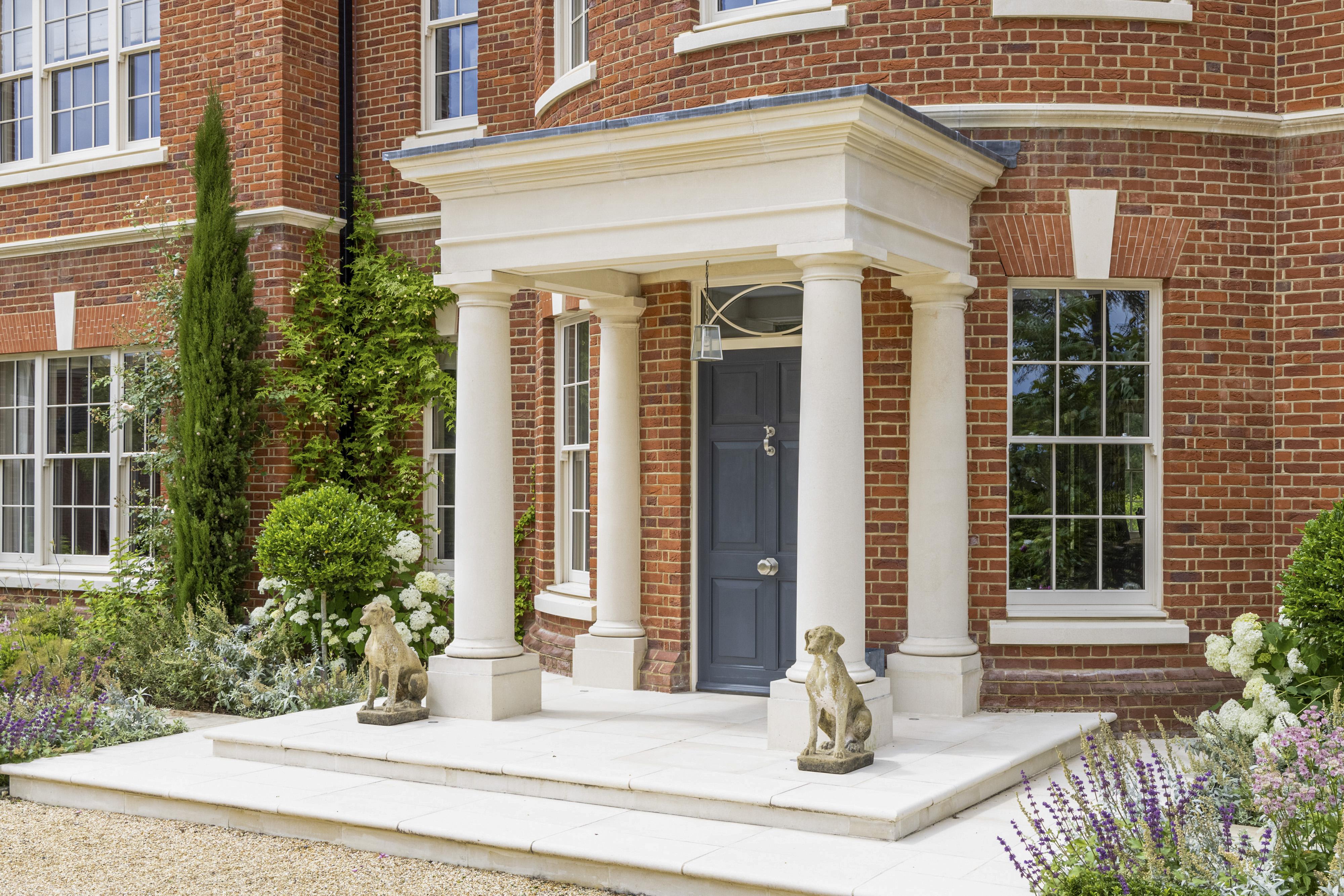 A red brick home with white stone portico