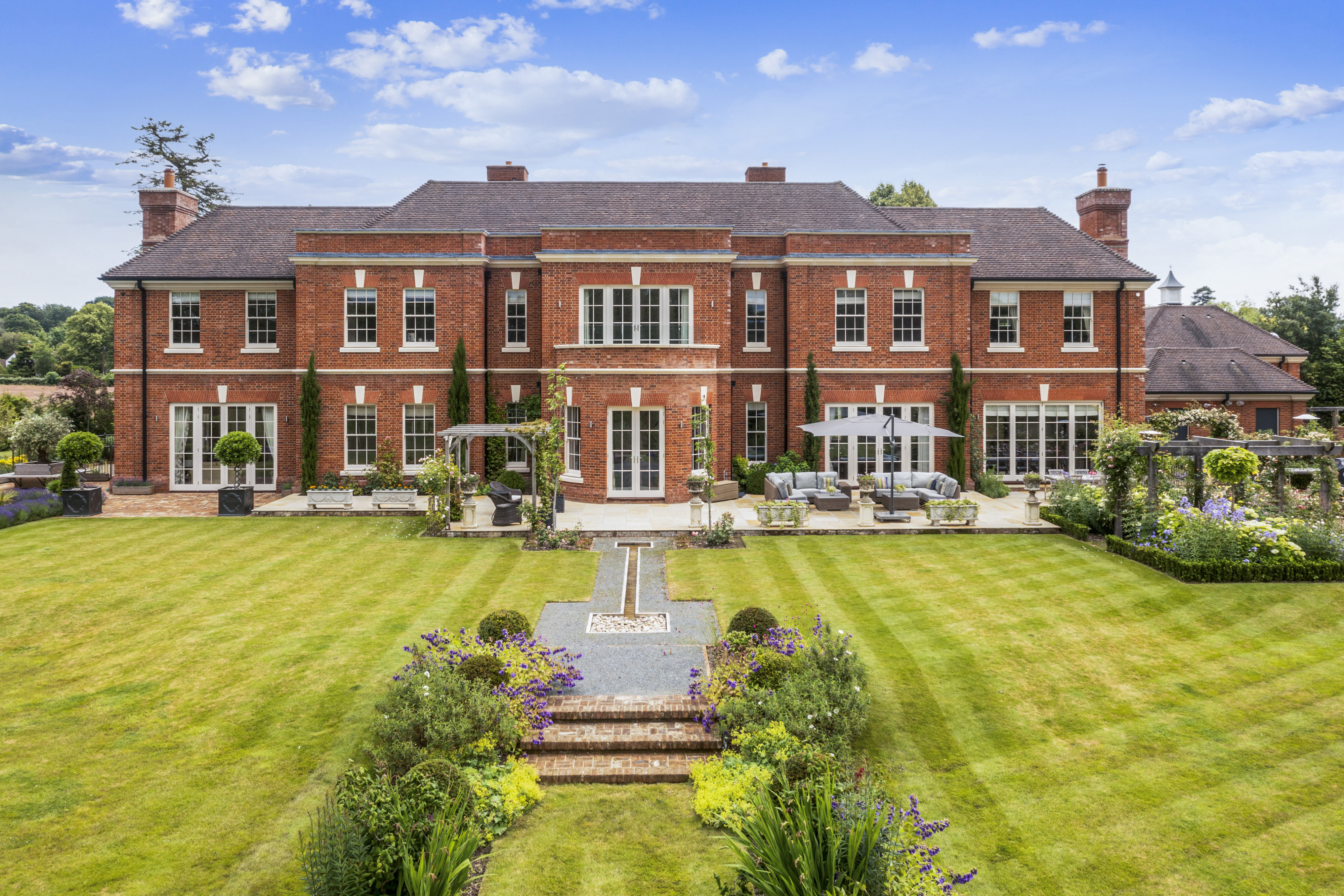 a red brick mansion with vast green grass