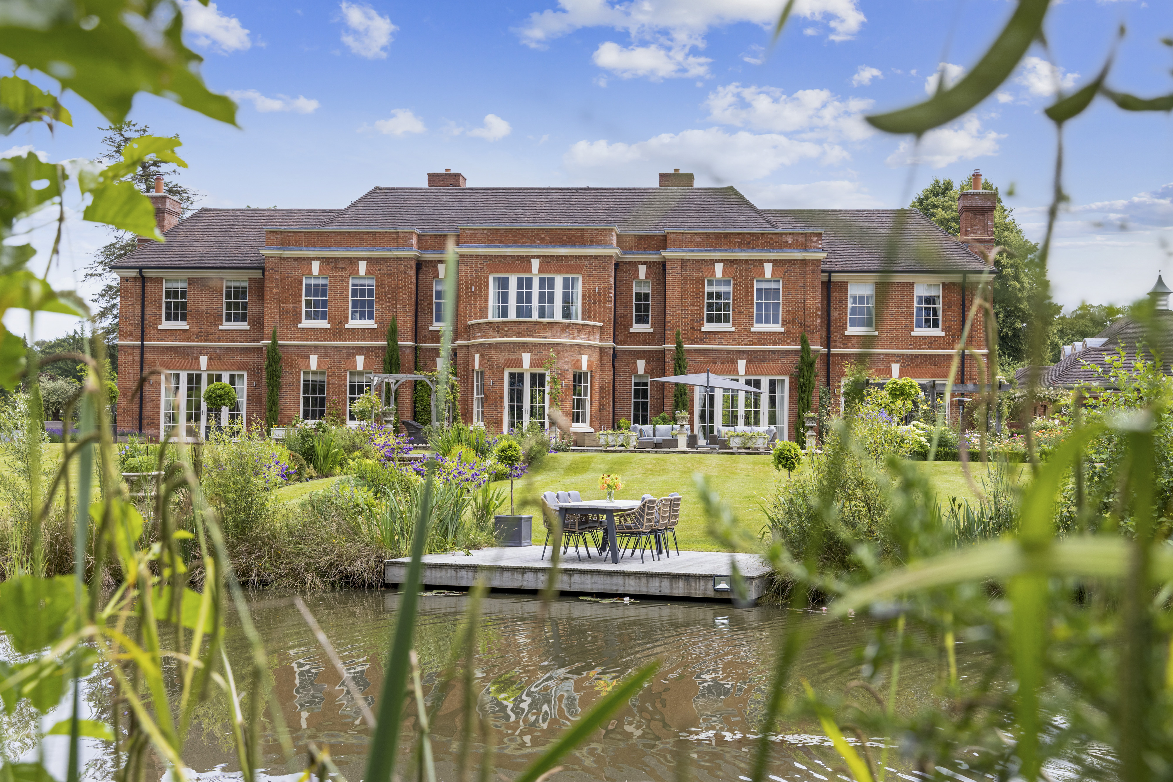 a red brick mansion overlooking a lake