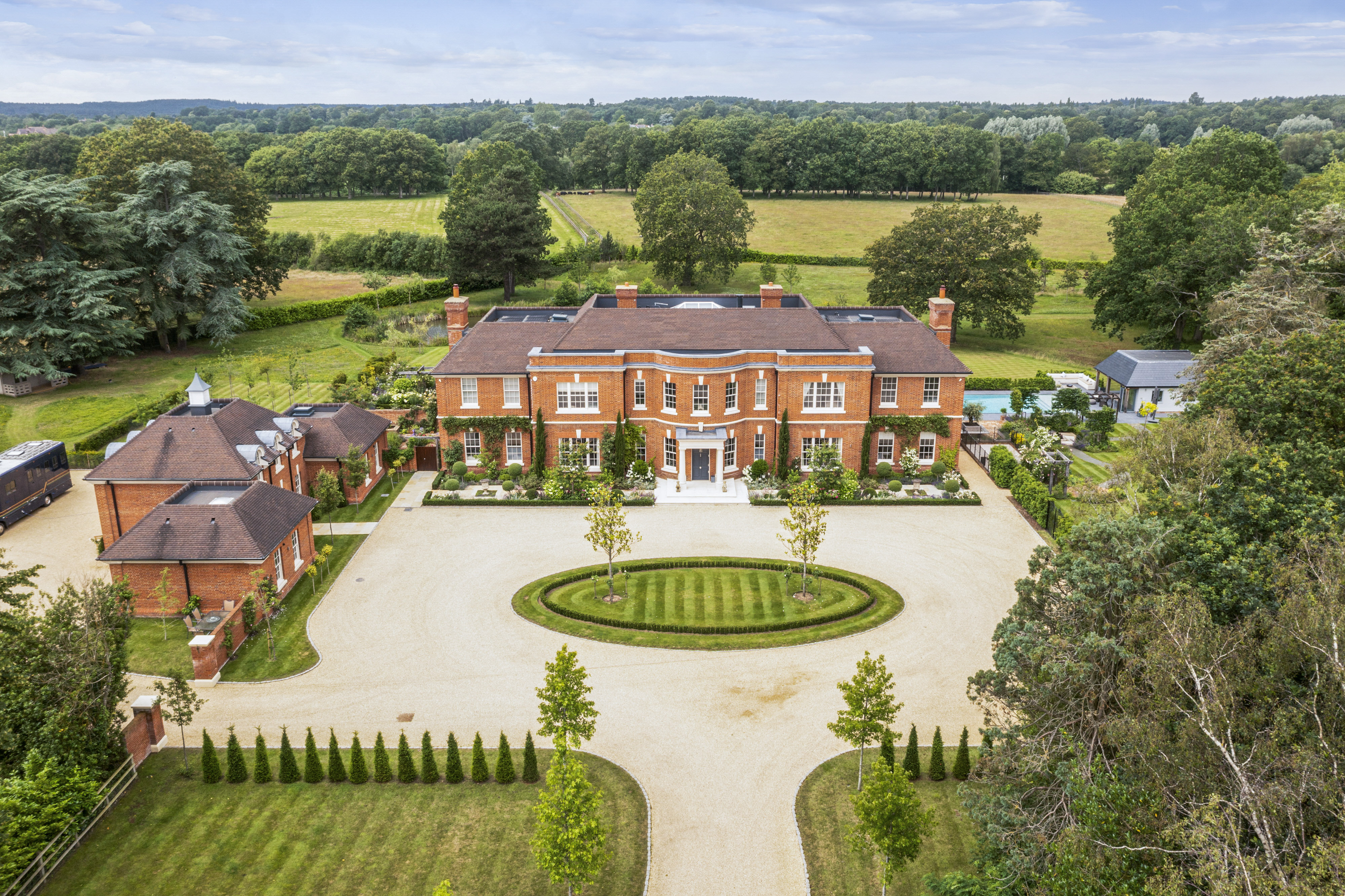 a red brick mansion with large gravel driveway and countryside scenery