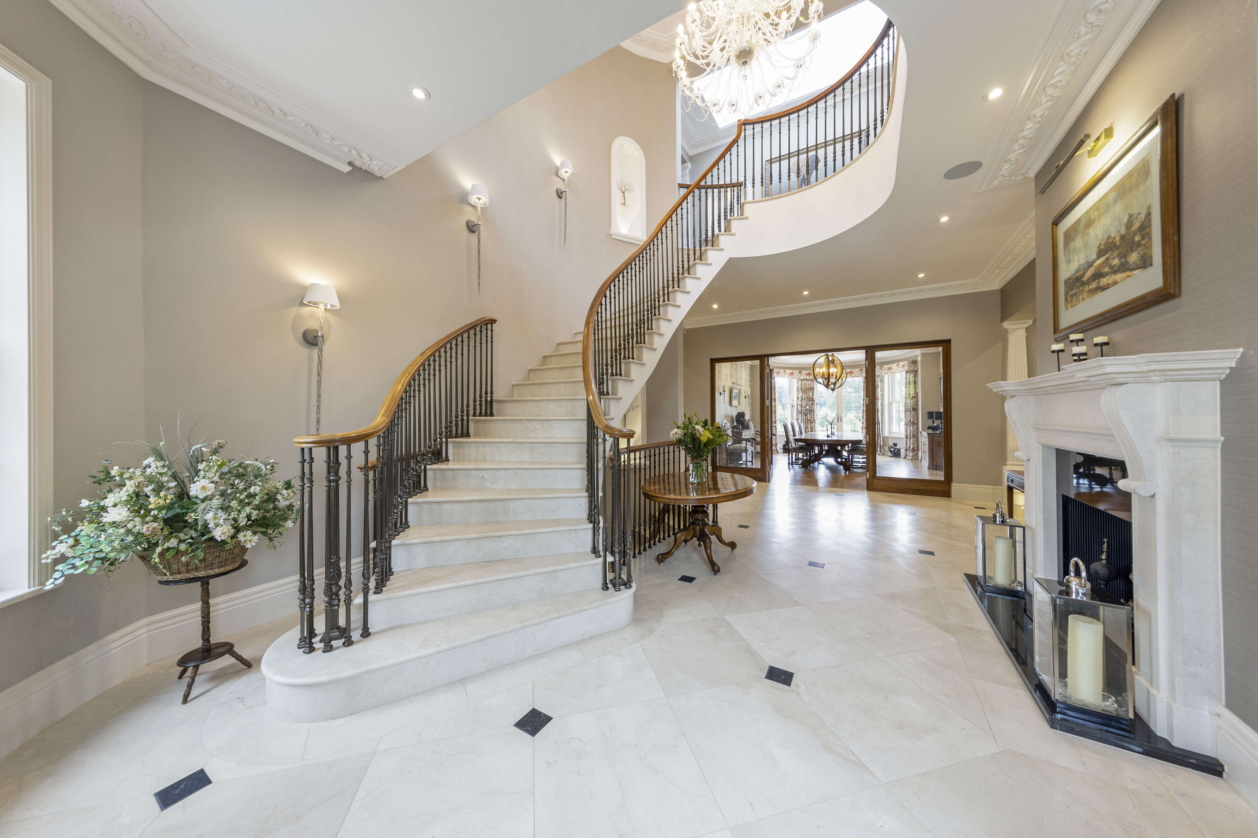 a grand entrance with sweeping staircase and marble floors