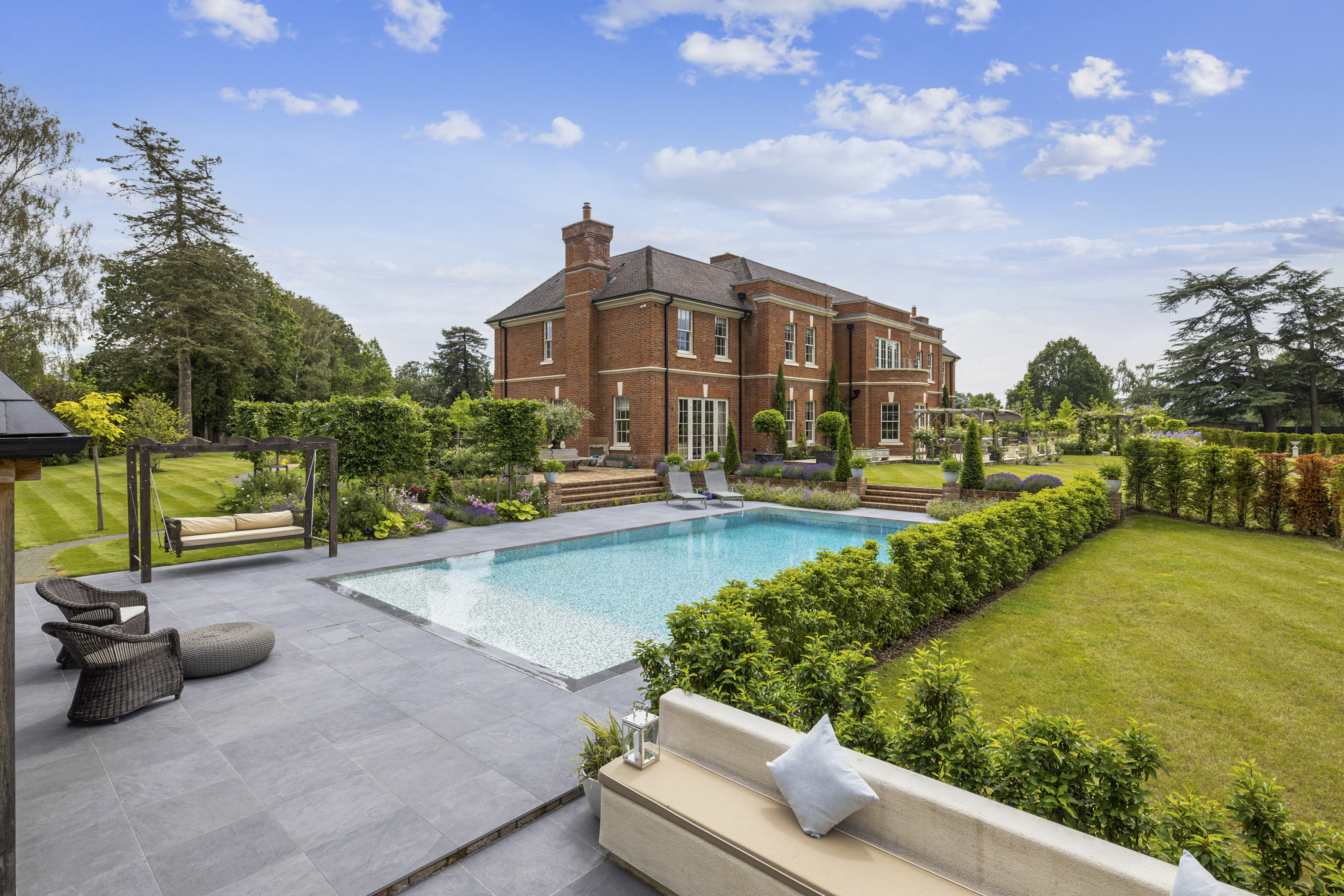 a red brick mansion with outdoor pool and seating area