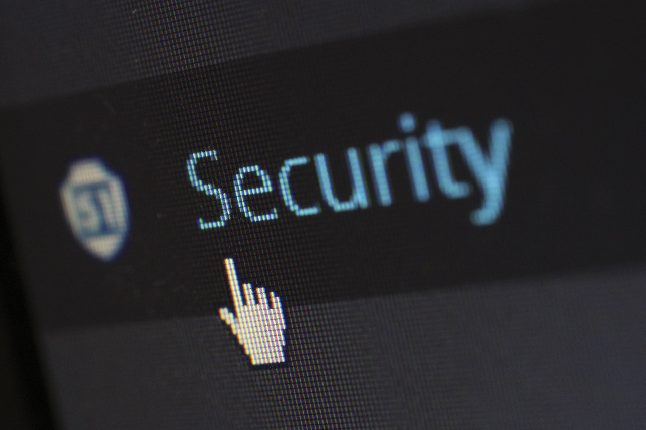 Pixelated view of the word Security with a computer generated hand pointing to the letter S