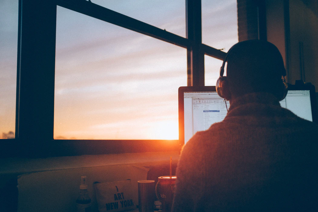 Employee focused working while sun sets outside the window