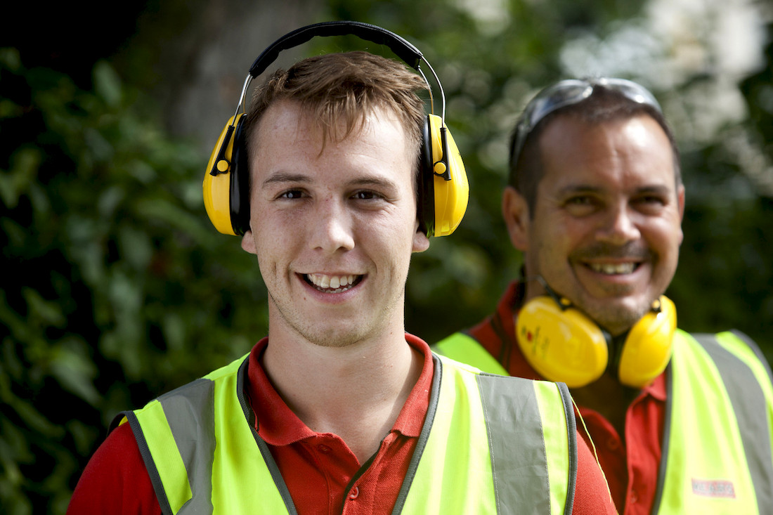 Two Mears employees smiling whilst wearing protective head phones