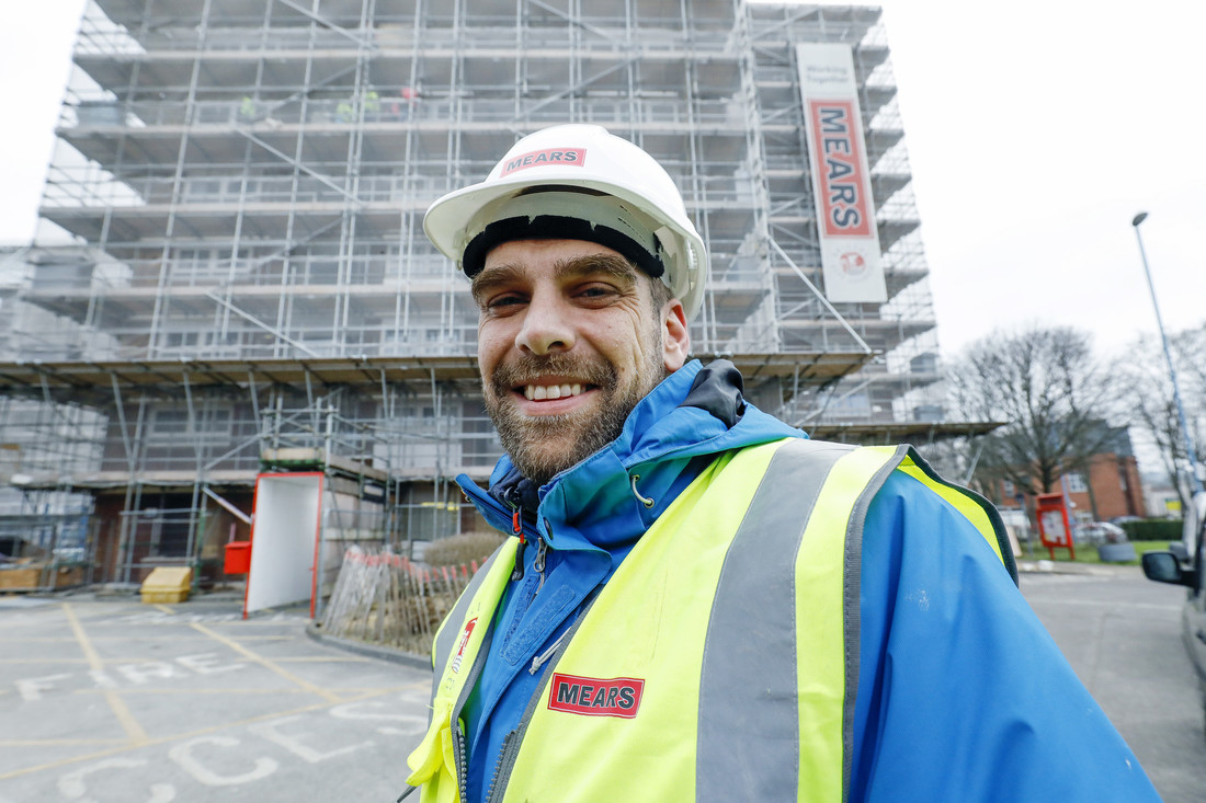 A Mears employee wearing a high vis and protective clothing smiling whilst stood in front of scaffolding