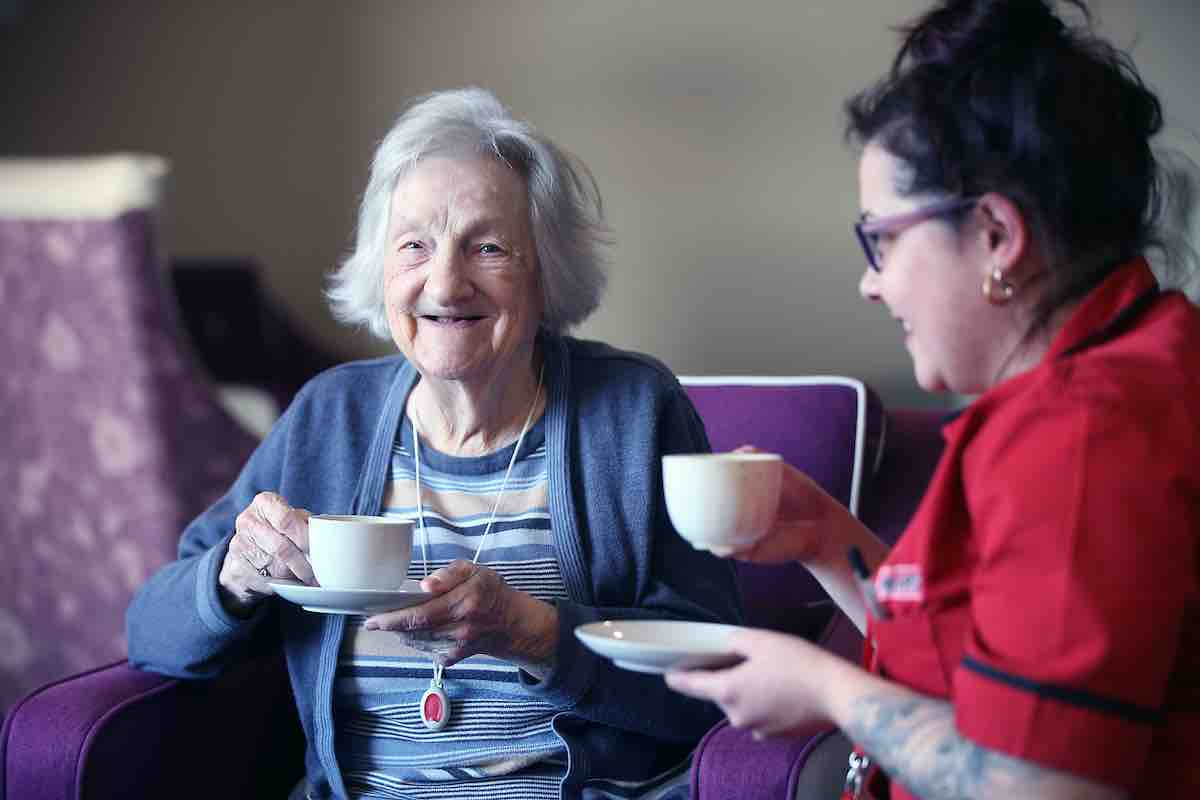 Mears carer drinking a cup of tea with a service user at Balmoral Place open day