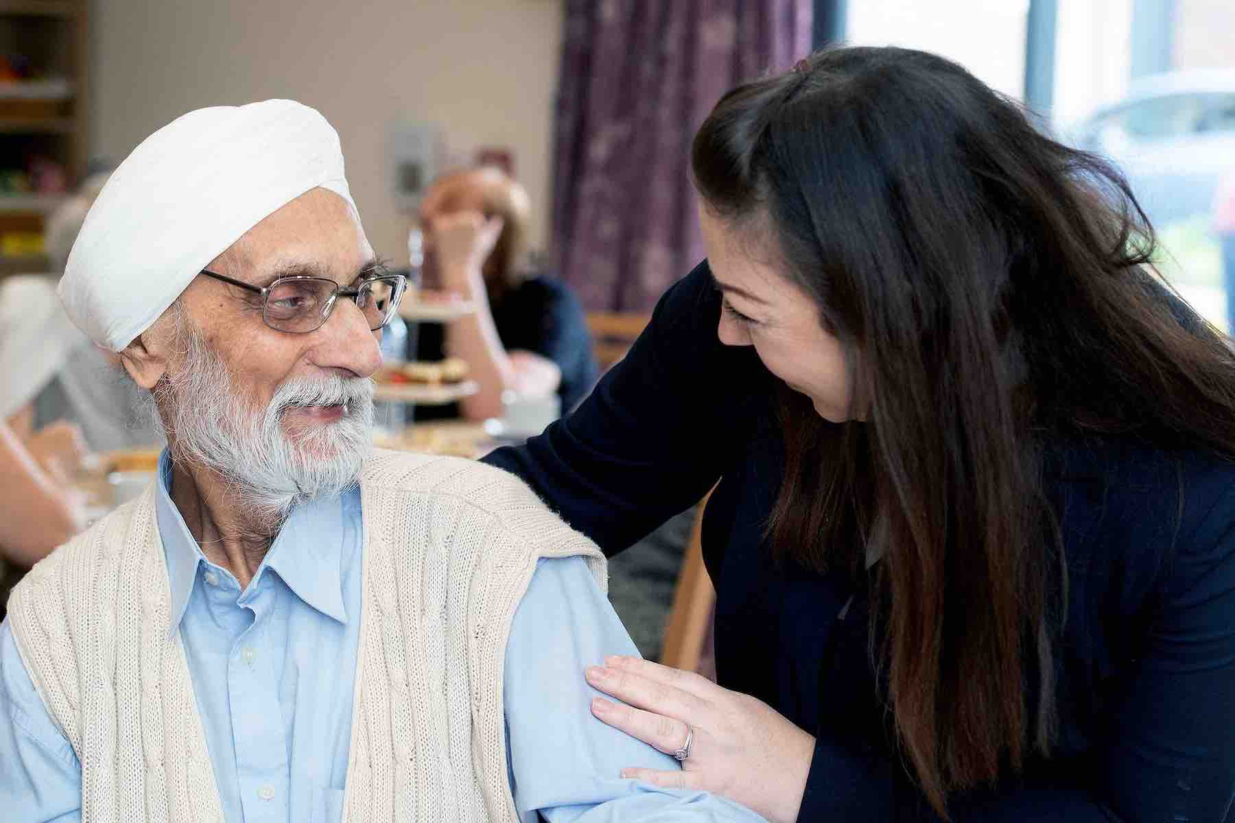 Mears carer with arm around service user, looking at each other