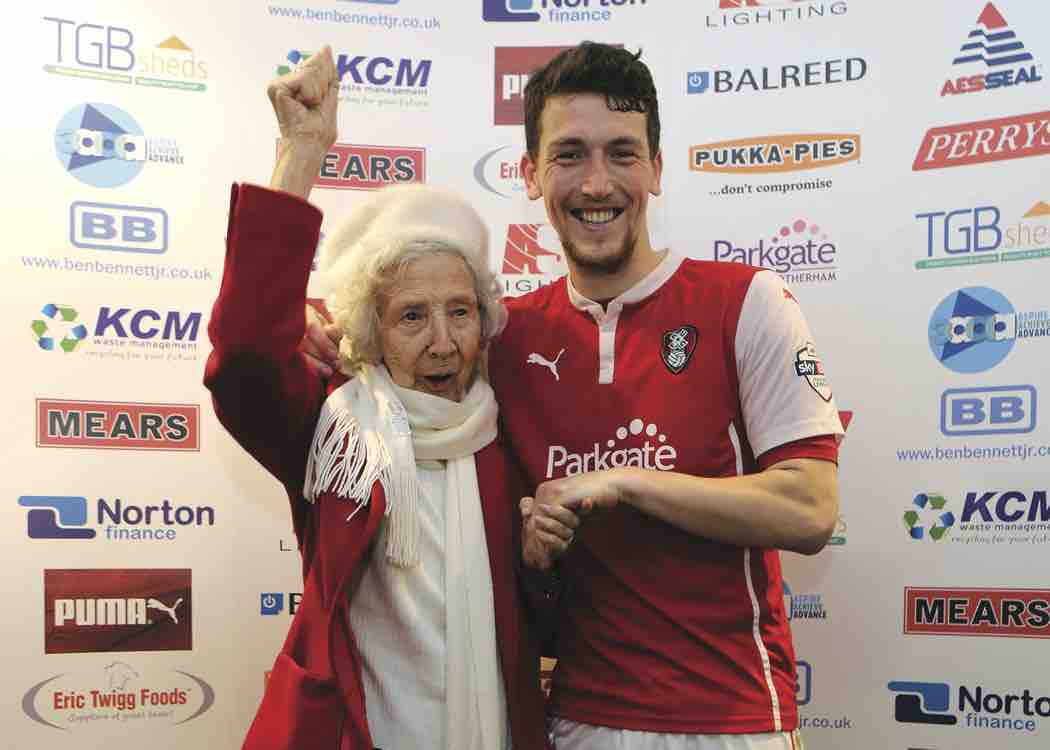 A football player standing next to an elderly lady whilst she is celebrating