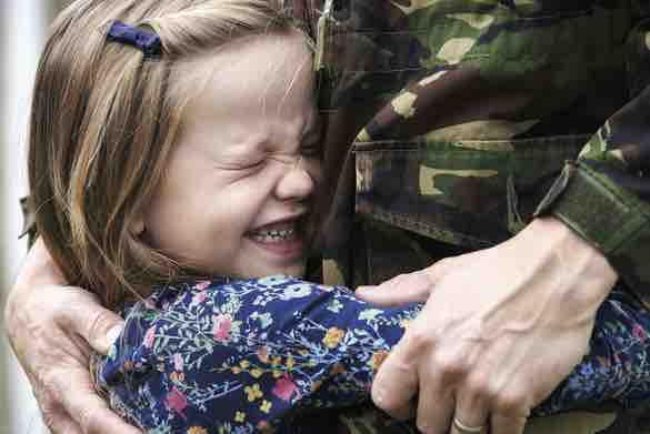 A young child cuddling a male dressed in camouflage