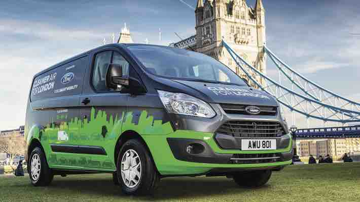 A green and black van parked outside of Tower Bridge in London