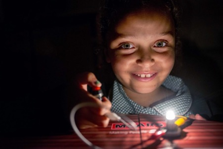 A smiling child in the dark with a small light