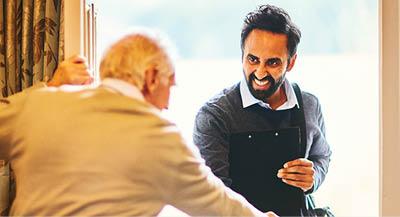 Man with clipboard greeting an elderly gentleman