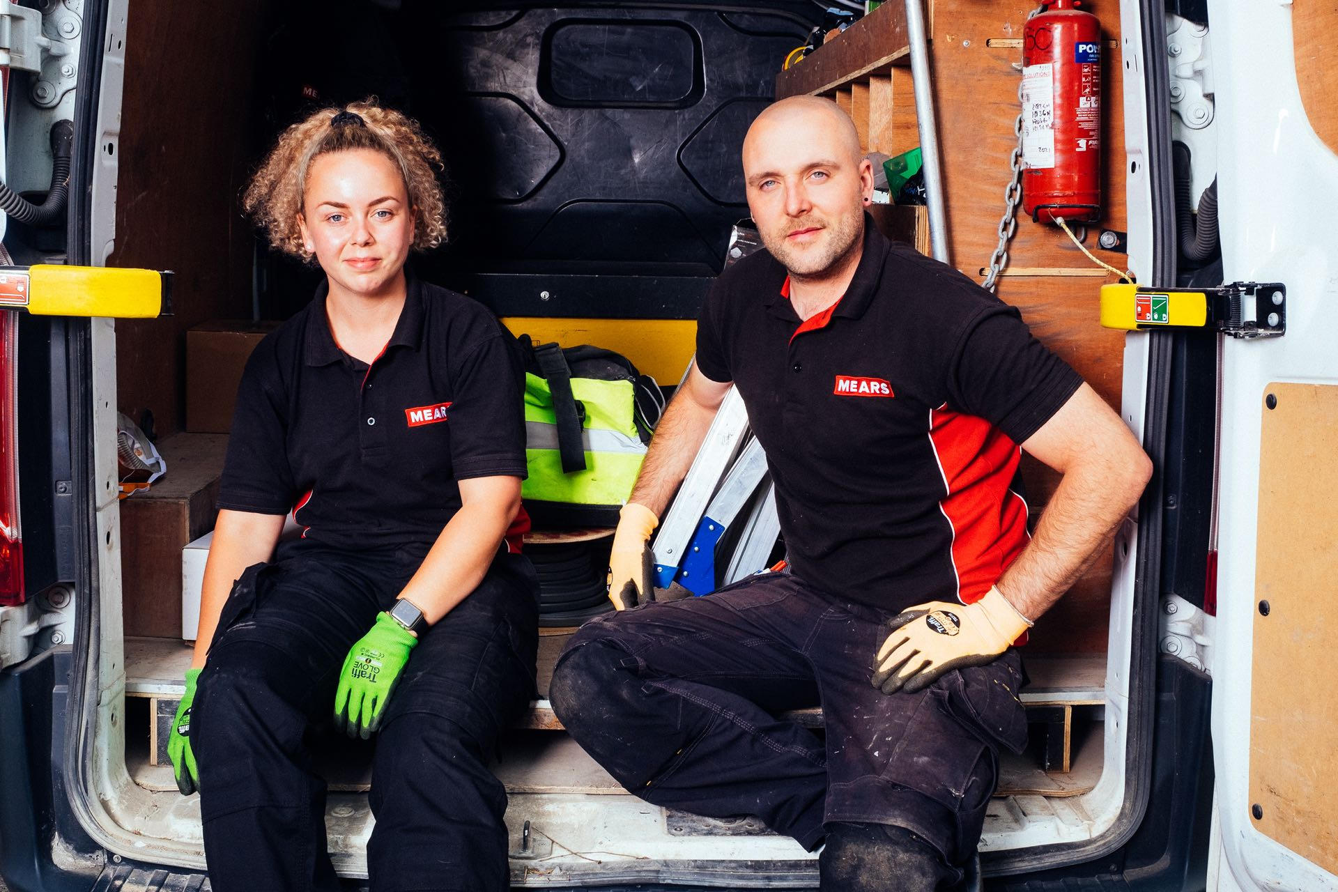 Two Mears colleagues sat in the back of a van wearing protective gloves
