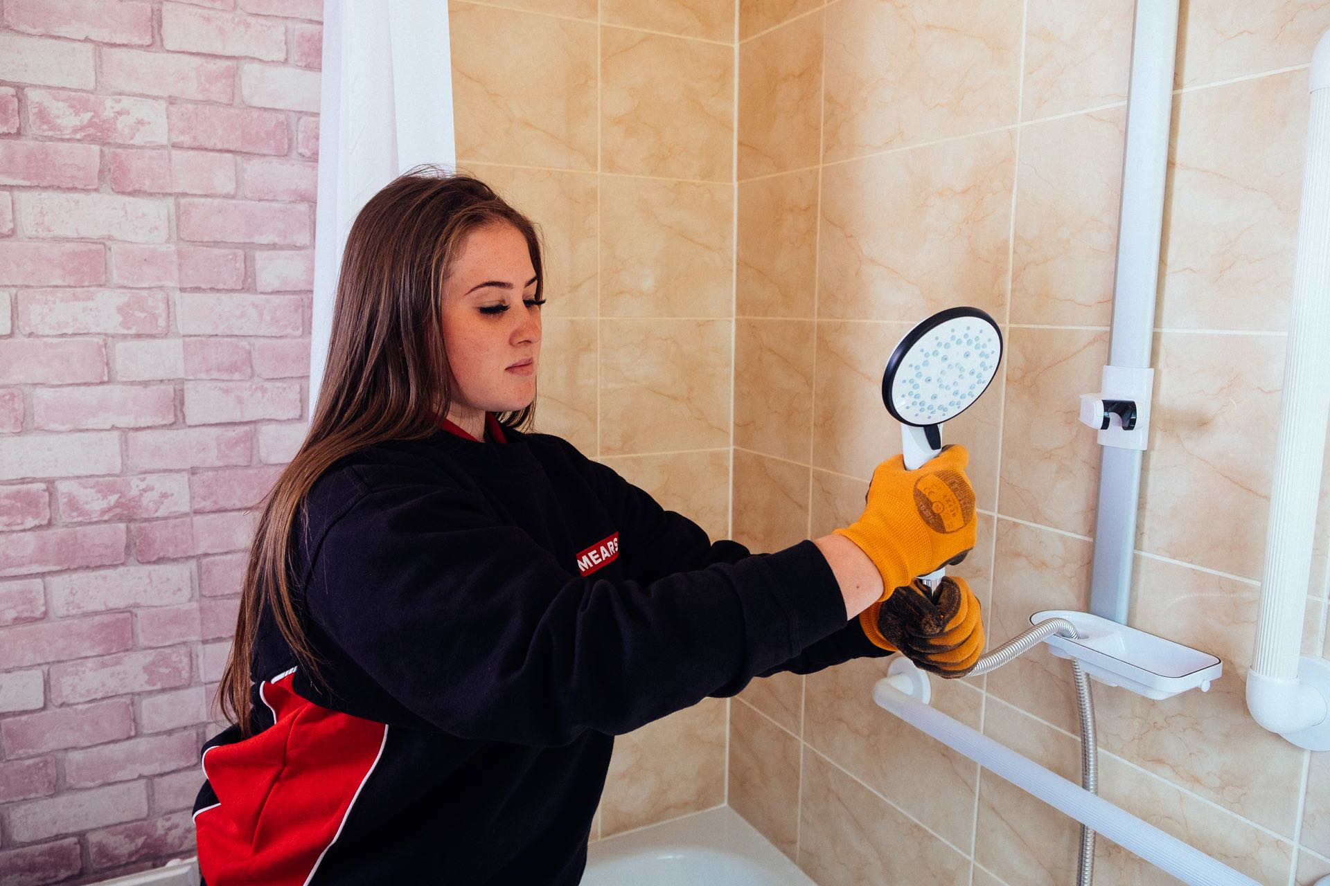 Mears colleague fixes shower fitting in bathroom