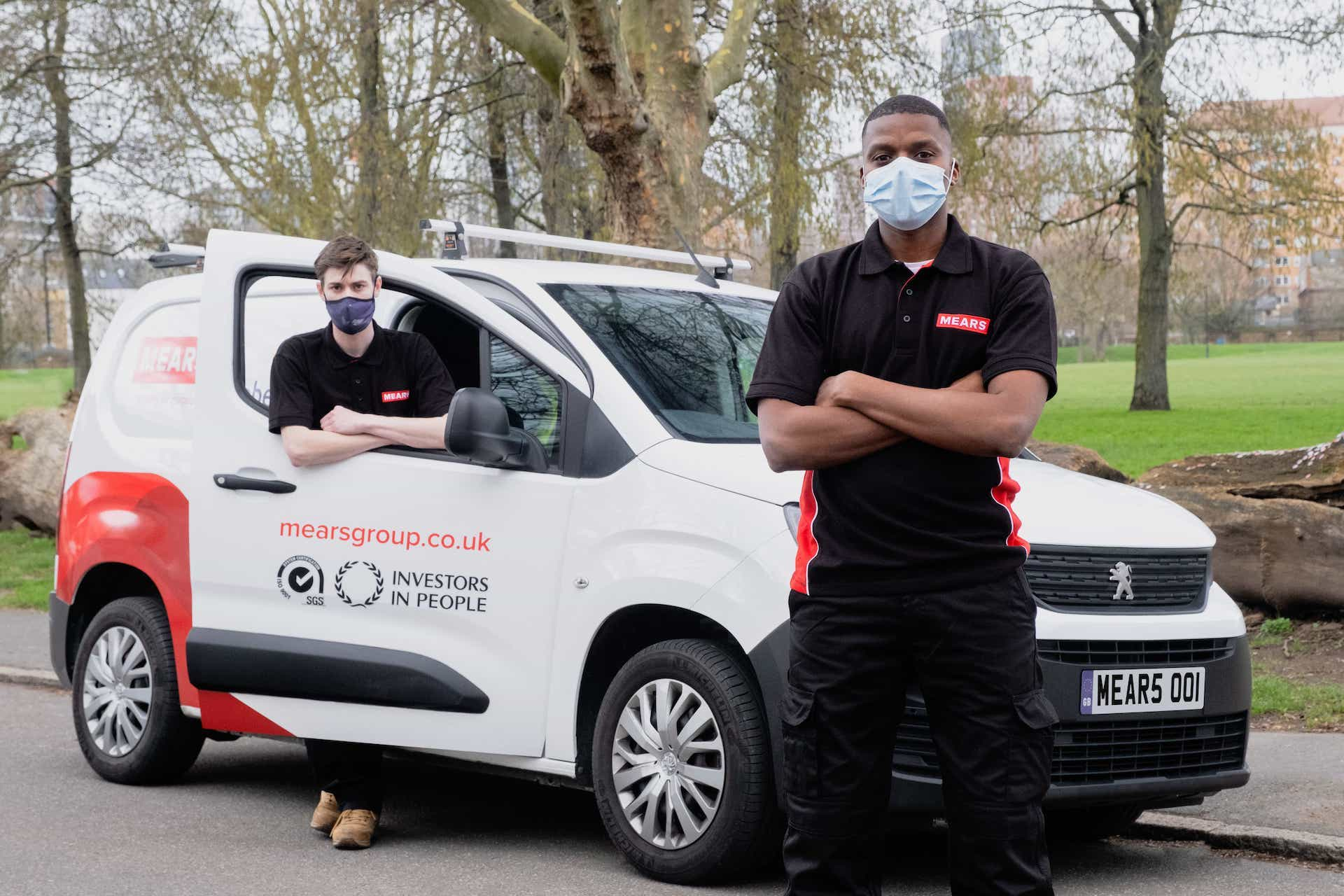 2 mears colleagues stood next to a mears van wearing face masks
