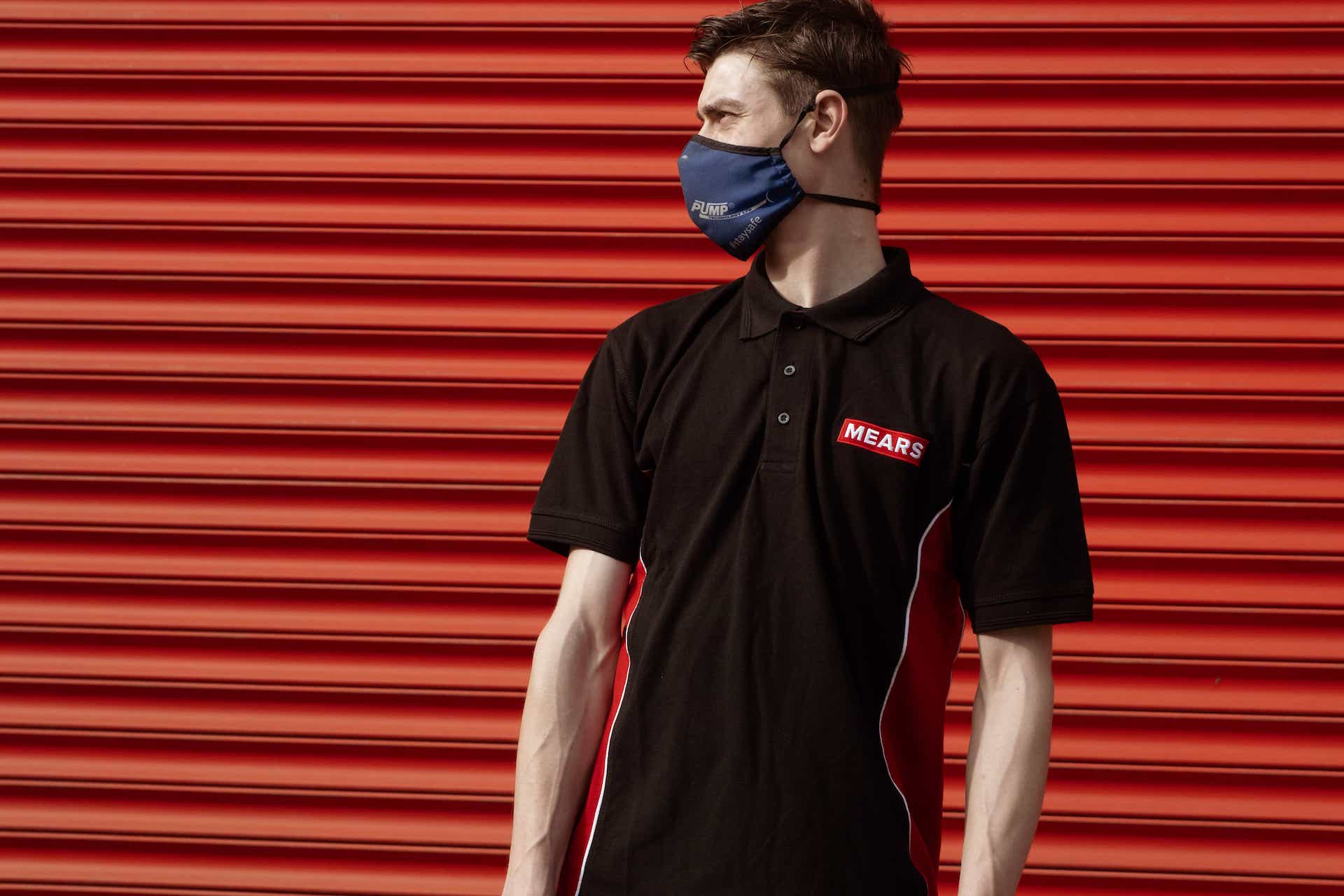Mears colleague stood in front of a red shutter wearing a face mask
