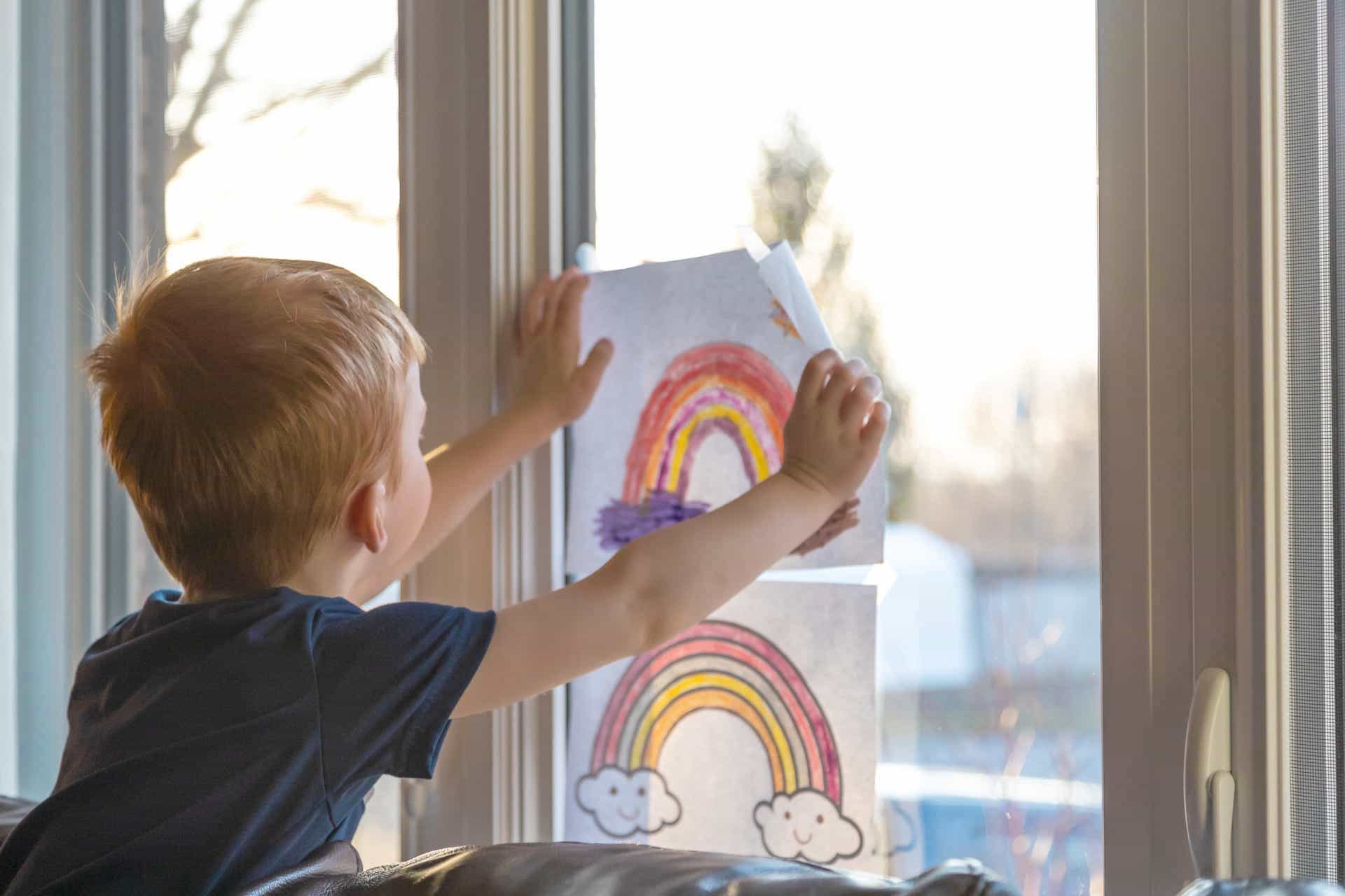 Boy holding up rainbow picture to a window
