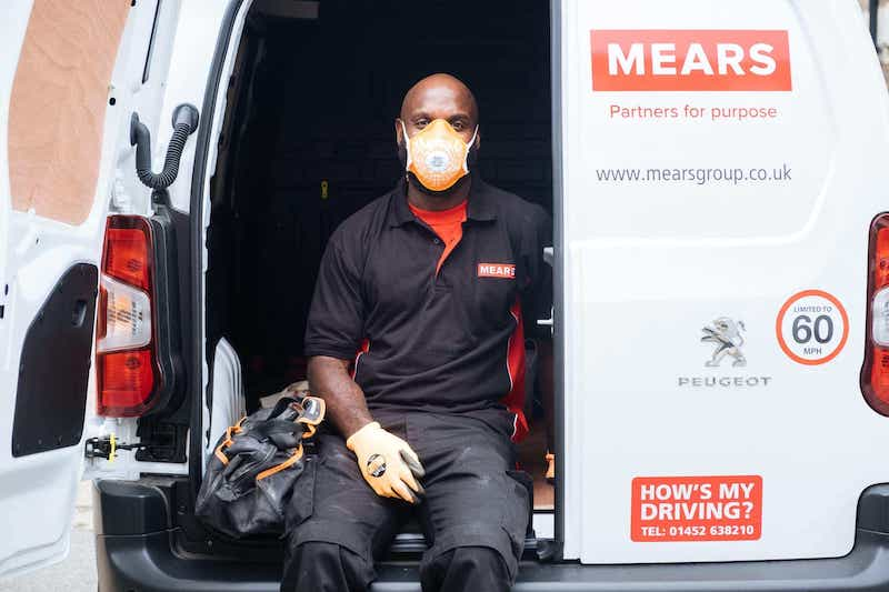 Mears colleague wearing a face mask sitting in the back of a van