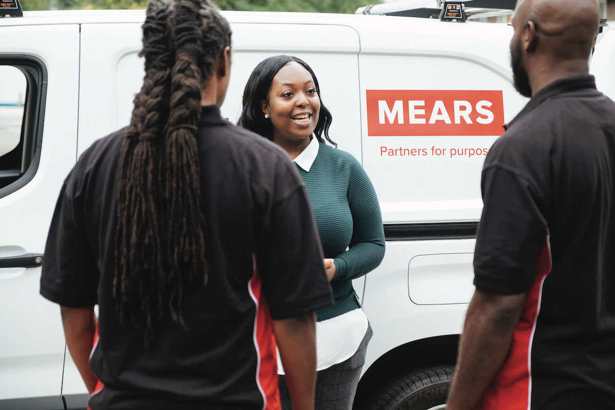 A female Mears colleague talking to 2 other Mears colleagues stood in front of a Mears van