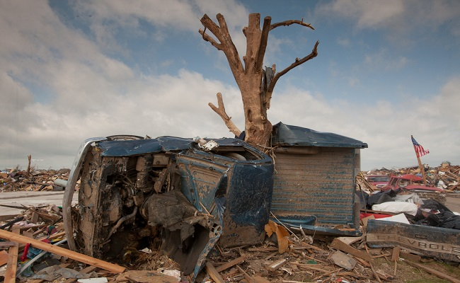 A destroyed truck wrapped around a tree.
