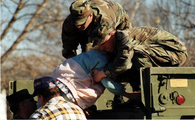 National Guardsmen help an elderly lady into a truck as town is evacuated.
