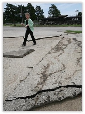 FEMA official looks at asphalt paving that has been moved by the pressure of strong flood waters.