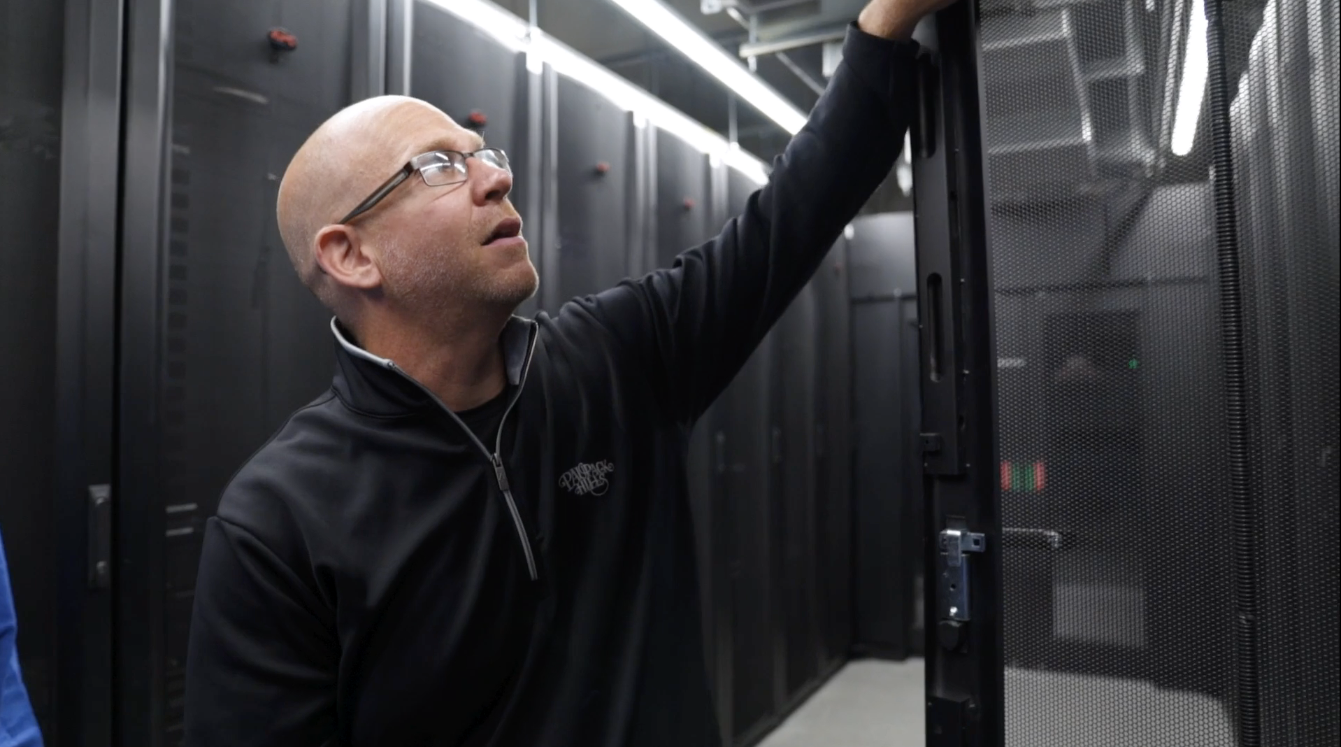 Image of man opening a server rack