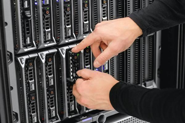 Hands working inside a server cabinet